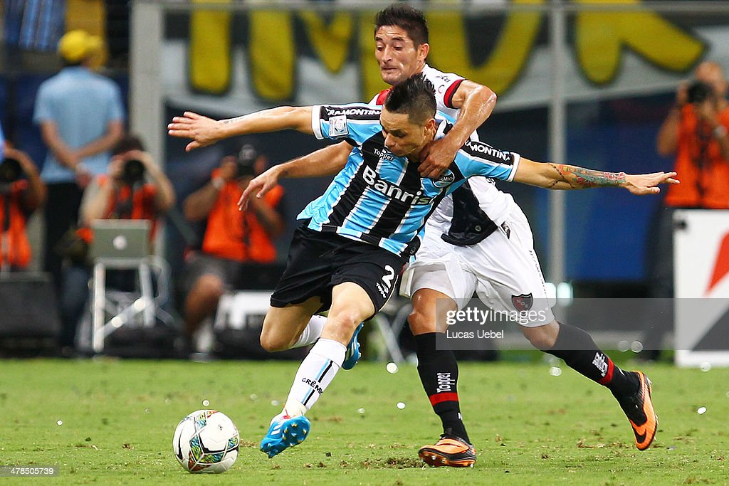 Para of Gremio and Ever Banega of Newell's Old Boys runs for the ball during the Copa Bridgestone Libertadores 2014 match between Gremio v Newell's Old Boys (ARG) at Arena do Gremio Stadium on March 13, 2014 in Porto Alegre, Brazil.