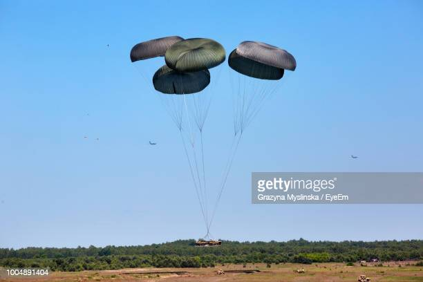 Parachute Flying Over Landscape Against Clear Sky