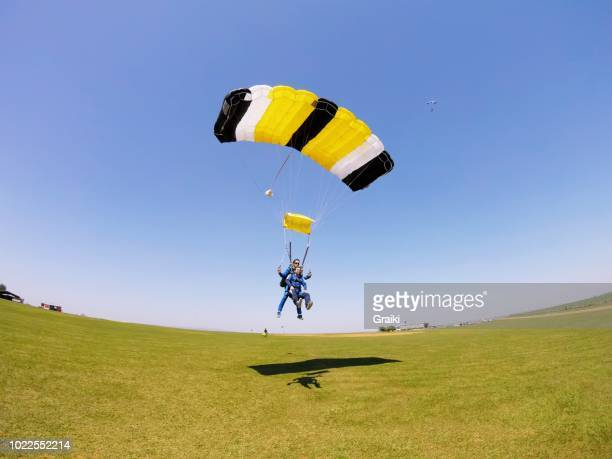 parachute tandem flying in the blue sky - fallschirm stock-fotos und bilder