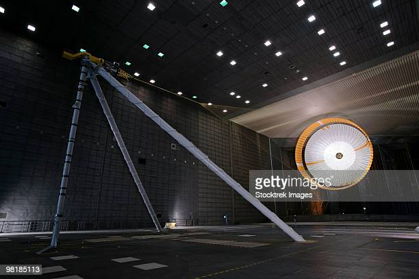 A parachute undergoes flight-qualification testing inside a wind tunnel.