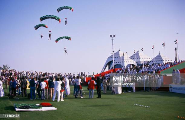 Parachutes in formation prepare to land on the 1st tee to mark the opening ceremony of the Emirates Golf Club the first green grass golf course in...