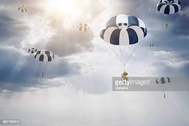 parachutes with dollar sign falling from sky - fallschirm stock-fotos und bilder