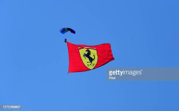 A parachutist displays a Scuderia Ferrari flag over the circuit prior to the F1 Grand Prix of Tuscany at Mugello Circuit on September 13 2020 in...
