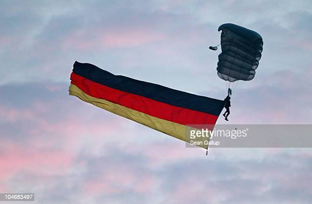 A parachutist of the German police force trails a German flag as he descends near the Reichstag seat of Germany's federal parliament on the day of...