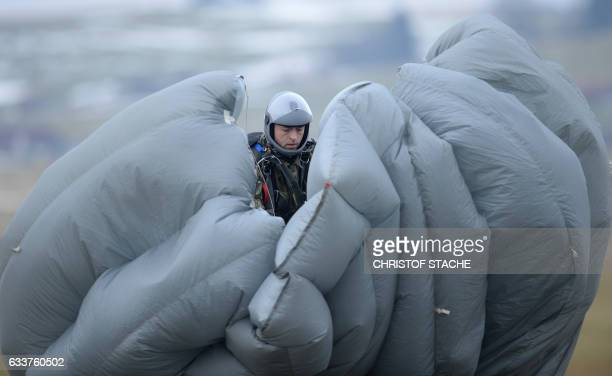 A parachutist soldier of the airborne and air transport group of the German army Bundeswehr grabs his parachute after his demonstration jump during...