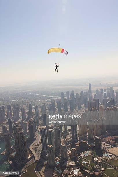 Parachutist under canopy flying over Dubai city