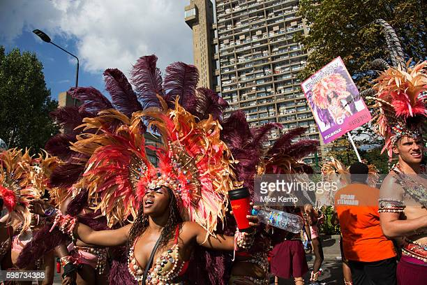 Parade dancers in feather costumes stop in the street at the base of Trellick Tower on Monday 28th August 2016 at the 50th Notting Hill Carnival in...