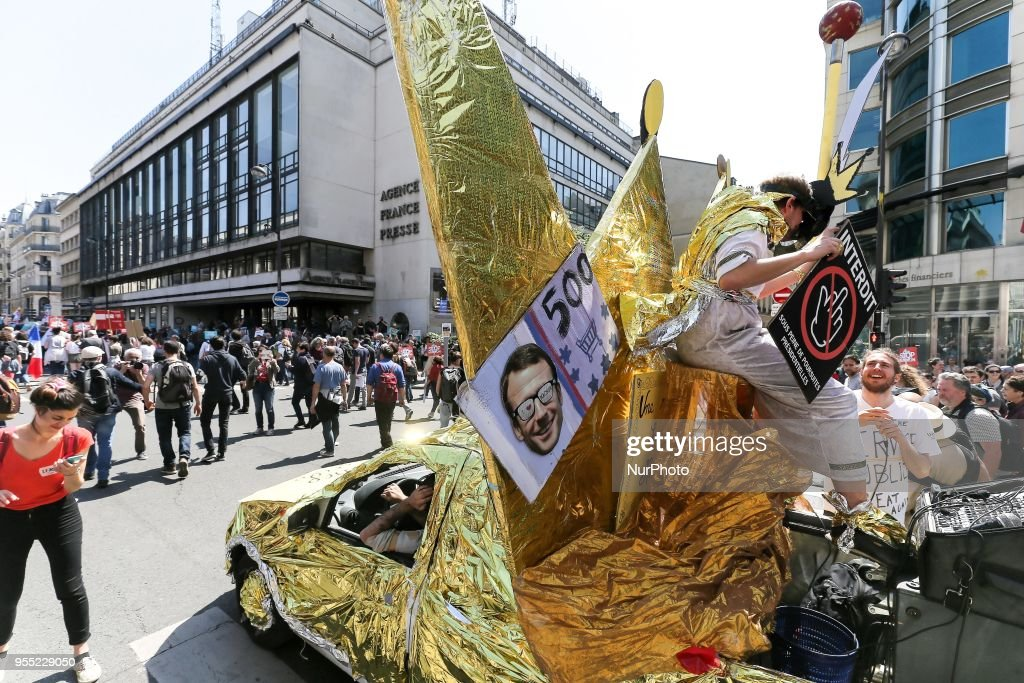 "A parade float mocking the French President in front of France Press Agency headquarters during a protest dubbed a ""Party for Macron"" (Fete a Macron) against the policies of the French president on the first anniversary of his election, on May 5, 2018, in Paris"