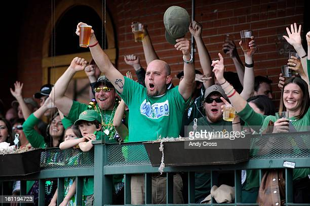 Parade goers at the Wynkoop Brewing Company celebrate as the Wynkoop Brewing Company float passes by them during the 50th annual Denver St Patrick's...