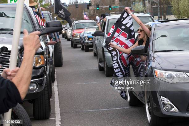 A parade of cars honk horns and show support for President Trump during a 'Hazardous Liberty Defend the Constitution' rally to protest the stayathome...