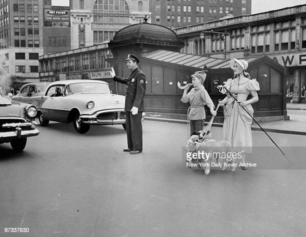 Parade of lambs marks the opening of Summer Festival Patrolman Ruben Kasten holds up traffic to permit Little Boy Blue Dickie Van and Little Bo Peep...