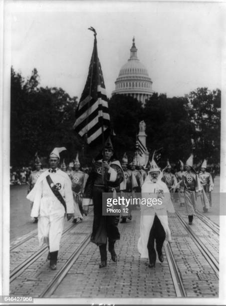 Parade of the Ku Klux Klan in regalia and carrying the US flag through counties of Virginia