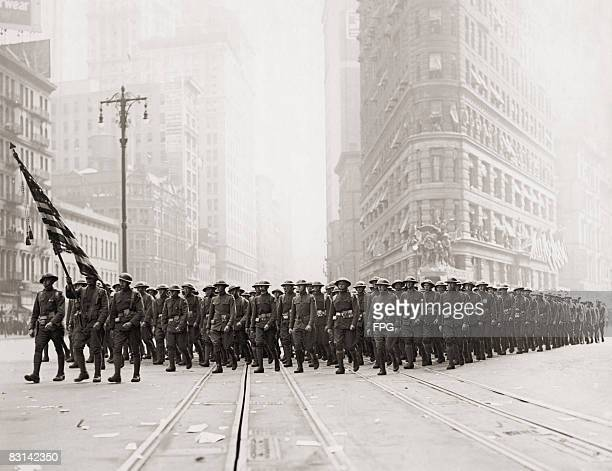 A parade of the US 2nd Infantry Division passes the Flatiron Building in New York circa 1918
