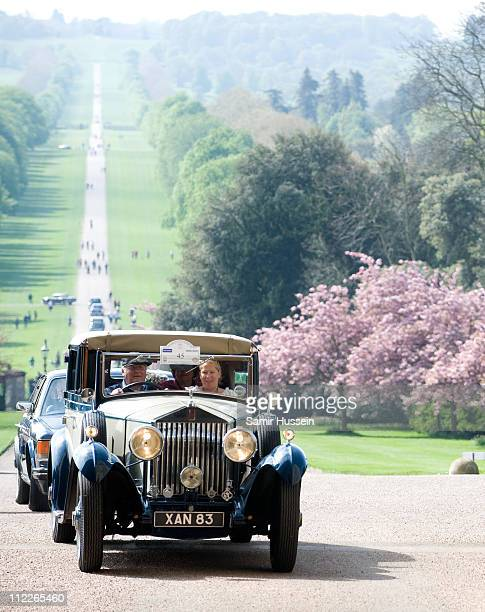 A parade of vintage RollsRocye and Bentley cars drive up the Long Walk into Windsor Castle on April 16 2011 in London England