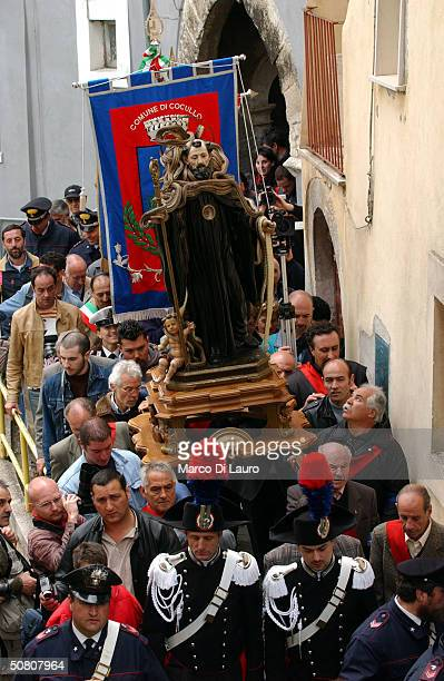 Parade participants carry the statue of St Dominic covered with snakes during the traditional snake procession in the village of Abruzzo May 6 2004...