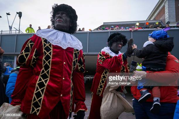 Parade participants dressed as Zwarte Piet distribute sweets to the children during the celebration of Sinterklaas' arrival on November 16 2019 in...