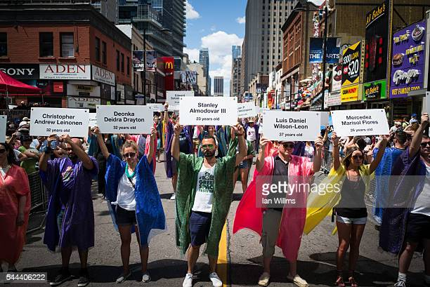 Parade participants from Grand Marshall Salah Bachir's float display the names of the Orlando shooting victims on Yonge Street during a moment of...