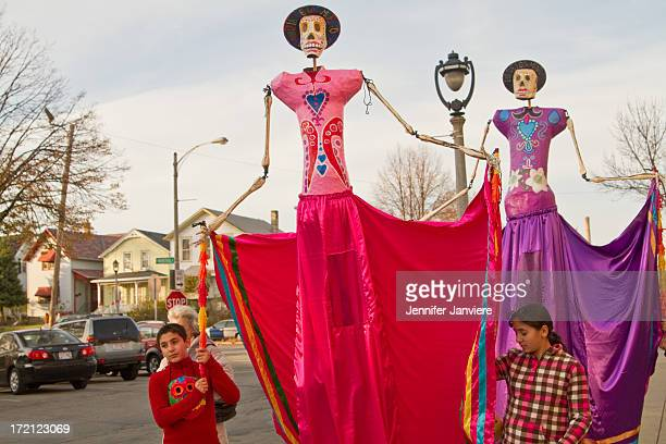 CONTENT] Parade participants hold large skeleton puppets at the Dia de los Muertos Parade in Milwaukee WI