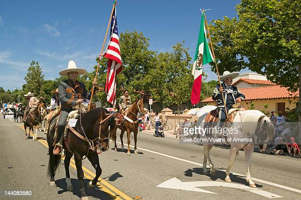 Parade participants on horseback carrying American and Mexican flags make their way down main street during a Fourth of July parade in Ojai CA