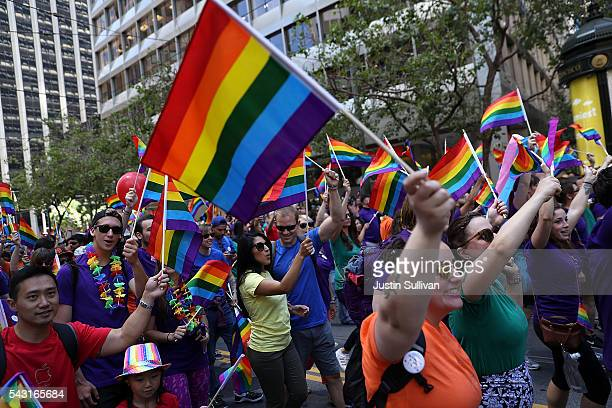 Parade participants wave pride flags as the march during the 2016 San Francisco Pride Parade on June 26, 2016 in San Francisco, California. Hundreds...