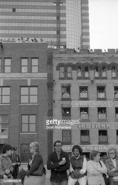 Parade spectators line the streets and rooftops of buildings as they watch the Brooklyn Bridge's 100th birthday celebrations in Brooklyn New York New...