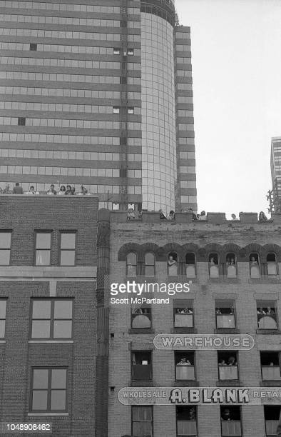 Parade spectators stand on rooftops and lean out windows as they watch the Brooklyn Bridge's 100th birthday celebrations in Brooklyn New York New...