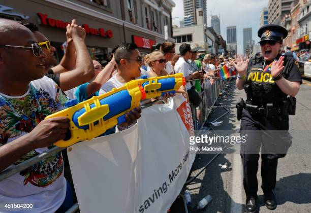 TORONTO JUNE 29 Parade watchers many who are armed with water guns soak some participants World Pride is celebrated during this year's Pride events...