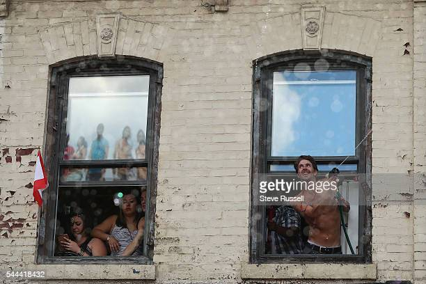 TORONTO ON JULY 3 Parade watchers spray water from windows during the the 2016 Toronto Pride parade along Yonge Street in Toronto July 3 2016
