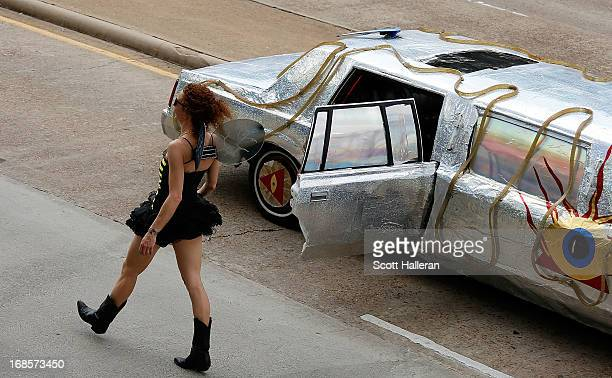A paradegoer passes an art car on Allen Parkway during the 26th Annual Houston Art Car Parade on May 11 2013 in Houston Texas