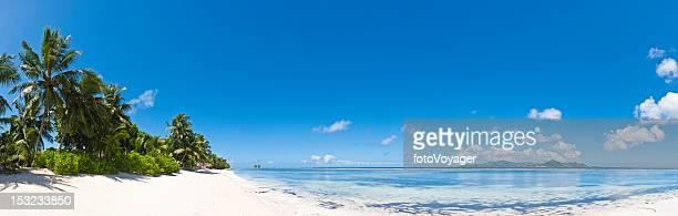 Paradise beach blue lagoon palm trees island retreat panorama Seychelles