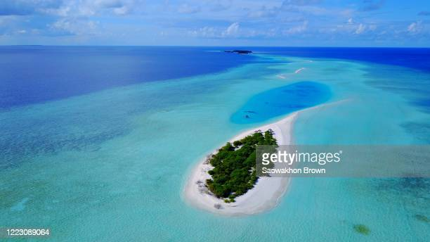 paradise gateway of tropical islands with large turquoise lagoon between, in the middle of deep blue ocean on a bright sky with clouds in maldives - islands in the sky stock pictures, royalty-free photos & images