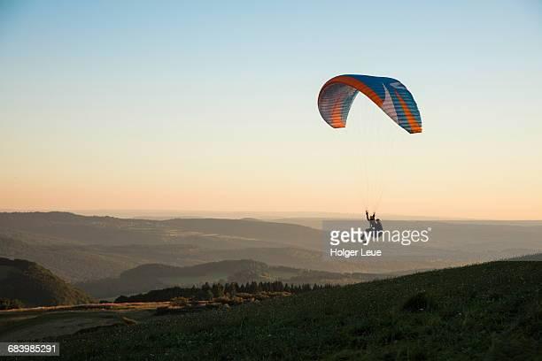 paraglider above wasserkuppe mountain at sunset - fallschirm stock-fotos und bilder
