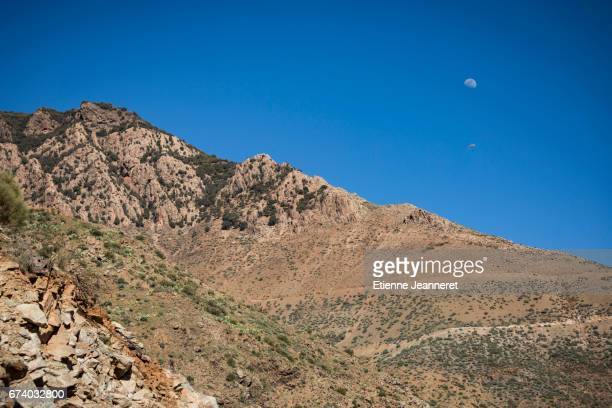 Paraglider and moon in blue sky over mountains, Maroc, 2017