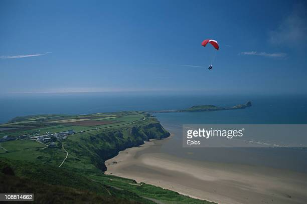 A paraglider enjoys spectacular views of the coastline at Rhossili and the Gower Peninsula Wales June 1997