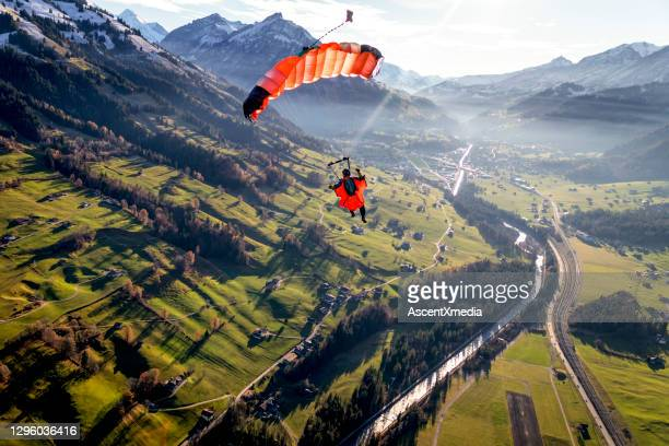 paraglider flies through clear skies in the morning - direction stock pictures, royalty-free photos & images