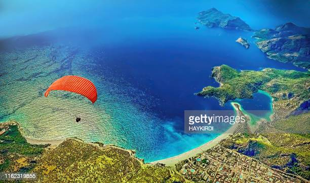 paraglider flying at fethiye over blue lagoon in oludeniz, turkey - aegean sea stock pictures, royalty-free photos & images