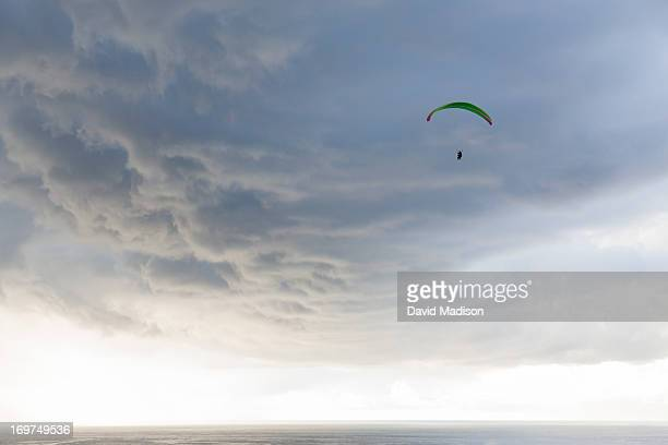 paraglider flying over the ocean - hgl stock pictures, royalty-free photos & images