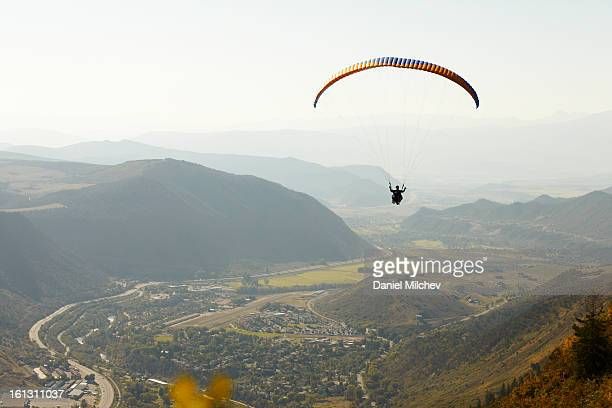 Paraglider flying over town, river and mountains.