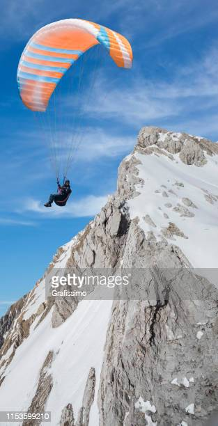 Paraglider flying parachute in the mountains