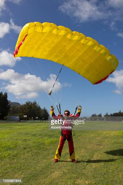paraglider glides towards landing, in field - landing touching down stock pictures, royalty-free photos & images