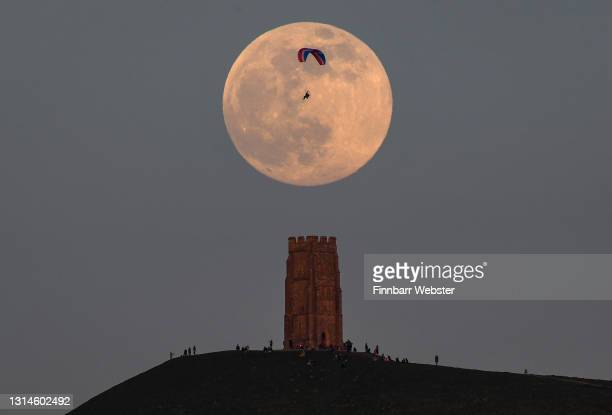 Paraglider is seen as the full moon rises behind Glastonbury Tor on April 26, 2021 in Glastonbury, England. The pink supermoon will reach peak size...