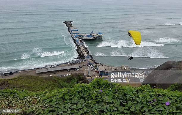 A paraglider is seen from the cliffs overlooking the Pacific Ocean in Lima's upscale neighbourhood of Miraflores on August 20 2016 / AFP / Daniel SLIM