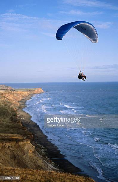 paraglider over compton bay. - compton bay isle of wight stock pictures, royalty-free photos & images