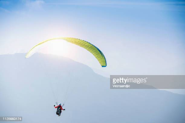 paraglider over mountains - glider stock photos and pictures