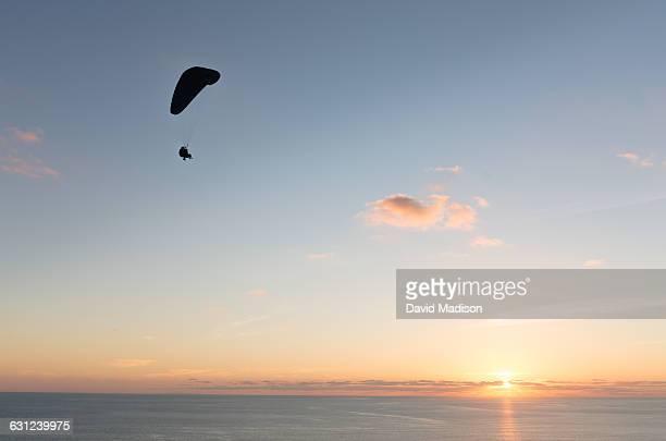 paraglider over ocean at sunset - hgl stock pictures, royalty-free photos & images