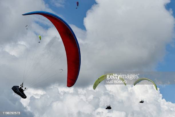 Paraglider pilots Remi Pickett of Britain and Juan Andrade of Trinidad and Tobago fly over the mountains in Roldanillo Valle del Cauca Department...