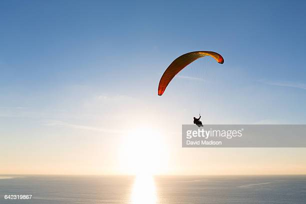 paraglider sailing over ocean at sunset - hgl stock pictures, royalty-free photos & images