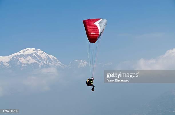 A paraglider sailing through the air Annapurna range in the background