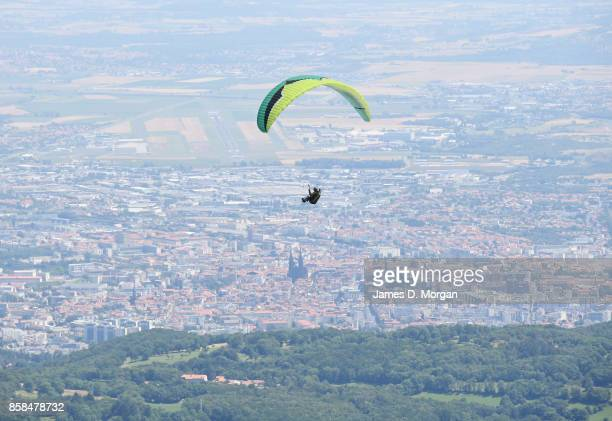 Paraglider soaring through the sky over country town in France in July 17th 2017