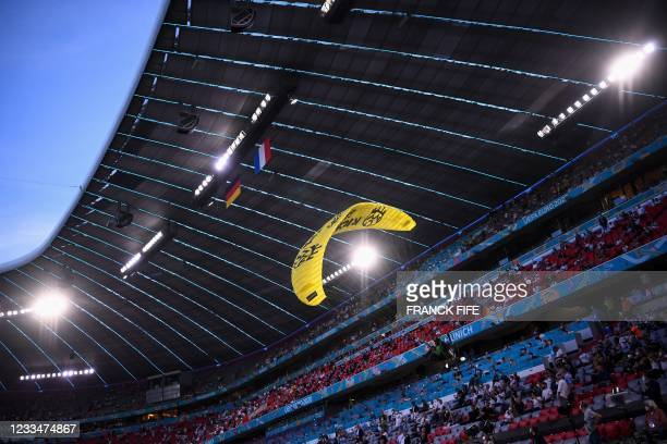 Paraglider sporting a message from environmental action group Greenpeace flies inside the stadium before the start of the UEFA EURO 2020 Group F...